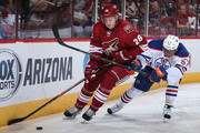 Michael Stone #26 of the Arizona Coyotes skates with the puck under pressure from David Perron #57 of the Edmonton Oilers during the first period of the NHL game at Gila River Arena on October 15, 2014 in Glendale, Arizona.  The Coyotes defeated the Oilers 7-4.