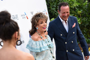 "Joan Collins and Percy Gibson attend the first ""Midsummer Party"" hosted by Elton John and David Furnish to raise funds for the Elton John Aids Foundation at the Villa Dorane on July 24, 2019 in Antibes, France."