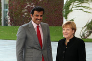 Sheikh Tamim bin Hamad Al Thani, the eighth and current Emir of the State of Qatar (L), arrives for a military welcome ceremony with German Chancellor Angela Merkel at the federal Chancellery on September 17, 2014 in Berlin, Germany. The Qatari monarch, known for his support of sporting events and his position as head of the Qatar Investment Authority board of directors, is visiting Berlin and Bavaria on his trip to the country.