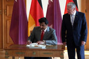 Sheikh Tamim bin Hamad Al Thani, the eighth and current Emir of the State of Qatar (L), signs the guest book as he meets with German President Joachim Gauck at Bellevue Palace on September 17, 2014 in Berlin, Germany. The Qatari monarch, known for his support of sporting events and his position as head of the Qatar Investment Authority board of directors, is visiting Berlin and Bavaria on his trip to the country.