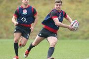 George Ford runs with the ball as Ben Youngs looks on during the England training session at Pennyhill Park on March 17, 2015 in Bagshot, England.