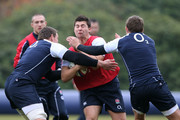 Scrumhalf Ben Youngs is tackled by Tom Johnson (L) and Toby Flood (R) during the England training session at Pennyhill Park on November 15, 2012 in Bagshot, England.