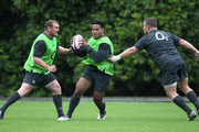 Manu Tuilagi moves between Tim Payne and Matt Stevens (R) during the England training session  at Pennyhill Park on June 20, 2011 in Bagshot, England.