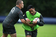 Manu Tuilagi is tackled by Matt Stevens during the England training session  at Pennyhill Park on June 20, 2011 in Bagshot, England.