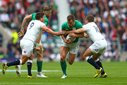 Tommy Bowe of Ireland is tackled by Ben Youngs (L) and George Ford of England (R) during the QBE International match between England and Ireland at Twickenham Stadium on September 5, 2015 in London, England.