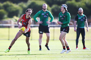 Jake Long runs with the ball from Andrew MGrath during an Essendon Bombers AFL training session at The Hangar on July 24, 2018 in Melbourne, Australia.
