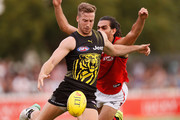 Kane Lambert of the Tigers kicks the ball under pressure from Jake Long of the Bombers during the JLT Community Series AFL match between the Essendon Bombers and the Richmond Tigers at Norm Minns Oval on February 24, 2018 in Wangaratta, Australia.