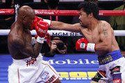 Manny Pacquiao (R) hits Yordenis Ugas in the first round of their WBA welterweight title fight at T-Mobile Arena on August 21, 2021 in Las Vegas, Nevada.