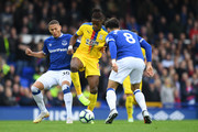 Wilfried Zaha of Crystal Palace battles for possession with Richarlison of Everton and André Gomes of Everton during the Premier League match between Everton FC and Crystal Palace at Goodison Park on October 21, 2018 in Liverpool, United Kingdom.