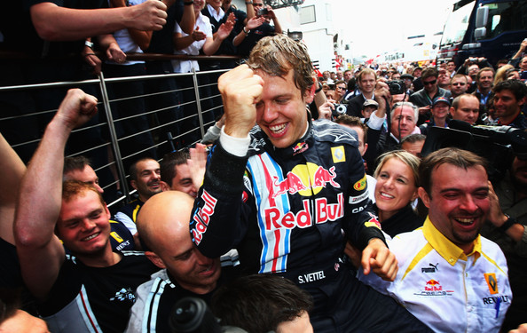 Sebastian Vettel of Germany and Red Bull Racing celebrates with team mates in the paddock after winning the British Formula One Grand Prix at Silverstone on June 21, 2009 in Northampton, England.