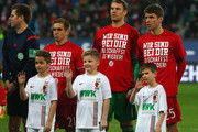 Philipp Lahm, Manuel Neuer and Thomas Mueller of Bayern Munich wear t-shirts showing support for injured team mate Holger Badstuber as they line up prior the Bundesliga match between FC Augsburg and FC Bayern Muenchen at SGL Arena on February 14, 2016 in Augsburg, Germany.