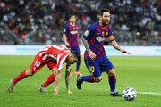 Lionel Messi of Barcelona avoids Angel Correa of Athletico Madrid during the Supercopa de Espana Semi-Final match between FC Barcelona and Club Atletico de Madrid at King Abdullah Sports City on January 09, 2020 in Jeddah, Saudi Arabia.