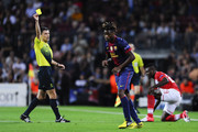 Alex Song of FC Barcelona (C) is shown a yellow card for a challenge on Emmanuel Emenike of FC Spartak Moscow (R) by the referee Milorad Mazic during the UEFA Champions League Group G match between FC Barcelona and FC Spartak Moscow at Camp Nou on September 19, 2012 in Barcelona, Spain.