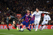 Lionel Messi of Barcelona holds off Sergio Ramos of Real Madrid during the Liga match between FC Barcelona and Real Madrid CF at Camp Nou on December 18, 2019 in Barcelona, Spain.
