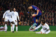 Luis Suarez of Barcelona is tackled by Sergio Ramos of Real Madrid during the Liga match between FC Barcelona and Real Madrid CF at Camp Nou on December 18, 2019 in Barcelona, Spain.