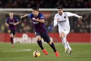 Luis Suarez of Barcelona battles for possession with Cristiano Piccini of Valencia during the La Liga match between FC Barcelona and Valencia CF at Camp Nou on February 2, 2019 in Barcelona, Spain.