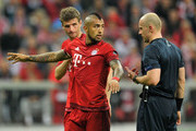 Thomas Mueller (L-R) and Arturo Vidal of Bayern Muenchen talk to referee Szymon Marciniak during the UEFA Champions League Quarter Final first leg match between FC Bayern Muenchen and SL Benfica at Allianz Arena on April 5, 2016 in Munich, Germany.