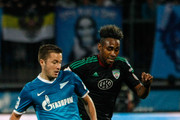 Viktor Fayzulin of FC Zenit St. Petersburg (L) passes the ball as Kanu of FC Terek Grozny defends during the Russian Football League Championship match between FC Zenit St. Petersburg and FC Terek Grozny at the Petrovsky stadium on September 14, 2013 in St. Petersburg, Russia.