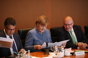 German Chancellor Angela Merkel reads a document while sitting between Forign Minister Sigmar Gabriel (L) and Minister of the Chancellery Peter Altmeier at the first government cabinet meeting since the collapse of talks over a new government coalition on November 22, 2017 in Berlin, Germany. While the previous German government is still functoning as normal, the creation of a new government following federal elections last September is in limbo after the collapse of coalition talks last Sunday between the Christian Democrats (CDU/CSU), the Free Democrats (FDP) and the Greens Party (Buendnis 90/Die Gruenen). Currently the most likely course is new elections in coming months.