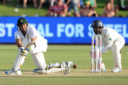 Imran Tahir (L) of South Africa plays a shot in front of Kaushal Silva of Sri Lanka during day two of the 1st Test match between South Africa and Sri Lanka at Supersport Park on December 16, 2011 in Pretoria, South Africa.