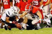 David Hinds #11 of the Florida Atlantic Owls forces a fumble and turnover by Arthur Lynch #88 of the Georgia Bulldogs that was recovered by Jeremy McKnight #26 at Sanford Stadium on September 15, 2012 in Athens, Georgia.