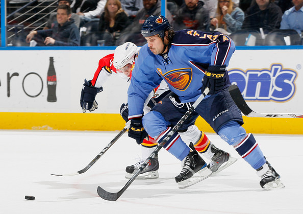 Zach Bogosian #4 of the Atlanta Thrashers controls the puck against Mike Santorelli #13 of the Florida Panthers at Philips Arena on November 17, 2010 in Atlanta, Georgia.