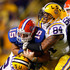 Harry Coleman Photos - Quarterback Tim Tebow #15 of the Florida Gators is tackled by Harry Coleman #24 and Rahim Alem #84 of the Louisiana State University Tigers at Tiger Stadium on October 10, 2009 in Baton Rouge, Louisiana. - Florida v LSU