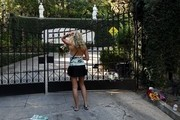 A fan pays her respects on September 28, 2017 at the main gate outside the Playboy Mansion home of Hugh Hefner, who died the previous day, in Beverly Hills, California. .The iconic Playboy Magazine was founded six decades ago by Hefner, who died on September 27 at the age of 91... / AFP PHOTO / Mark RALSTON