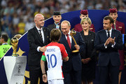 President of Russia Valdimir Putin greets Luka Modric of Croatia as FIFA President Gianni Infantino and French President Emmanuel Macron looks on during the 2018 FIFA World Cup Final between France and Croatia at Luzhniki Stadium on July 15, 2018 in Moscow, Russia.