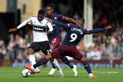 Alexandre Lacazette and Danny Welbeck of Arsenal tackle Andre-Frank Zambo Anguissa of Fulham during the Premier League match between Fulham FC and Arsenal FC at Craven Cottage on October 7, 2018 in London, United Kingdom.