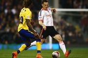 Scott Parker of Fulham is watched by Gaetan Bong of Wigan Athletic during the Sky Bet Championship match between Fulham and Wigan Athletic at Craven Cottage on April 10, 2015 in London, England.
