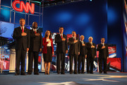 Republican presidential candidates (L-R) Jon Huntsman, Herman Cain, Rep. Michele Bachmann (R-MN), former Massachusetts Gov. Mitt Romney, Texas Gov. Rick Perry, Rep. Ron Paul, Newt Gingrich and Rick Santorum during the pledge of allegiance as they prepare to debate during the event sponsored by CNN and The Tea Party Express at the Florida State fairgrounds on September 12, 2011 in Tampa, Florida. The debate featured the eight candidates ten days before the Florida straw poll.