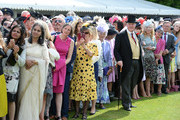 Guests watch the arrival of Queen Elizabeth II and the Prince Philip, Duke of Edinburgh at a garden party at Buckingham Palace on June 1, 2017in London, England.