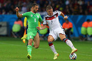 Bastian Schweinsteiger of Germany controls the ball against Djamel Mesbah of Algeria during the 2014 FIFA World Cup Brazil Round of 16 match between Germany and Algeria at Estadio Beira-Rio on June 30, 2014 in Porto Alegre, Brazil.