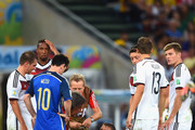 Bastian Schweinsteiger of Germany receives treatment as teammates Mesut Oezil, Toni Kroos, Philipp Lahm and Thomas Mueller look on with Lionel Messi during the 2014 FIFA World Cup Brazil Final match between Germany and Argentina at Maracana on July 13, 2014 in Rio de Janeiro, Brazil.