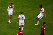 Thomas Mueller of Germany (L) reacts after scoring his team's first goal on a penalty kick with Mario Goetze (C) and Sami Khedira (R) during the 2014 FIFA World Cup Brazil Group G match between Germany and Portugal at Arena Fonte Nova on June 16, 2014 in Salvador, Brazil.