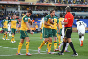 Harry Kewell (L) of Australia explains the ball hit his arm and Lucas Neill pleads with the referee as Roberto Rosetti sends off Kewell for handball and awards Ghana a penalty during the 2010 FIFA World Cup South Africa Group D match between Ghana and Australia at the Royal Bafokeng Stadium on June 19, 2010 in Rustenburg, South Africa.