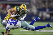Jimmy Graham #80 of the Green Bay Packers is tackled by Jeff Heath #38 of the Dallas Cowboys after catching a pass  at AT&T Stadium on October 6, 2019 in Arlington, Texas.  The Packers defeated the Cowboys 34-24.