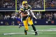 Jimmy Graham #80 of the Green Bay Packers is tackled by Jeff Heath #38 of the Dallas Cowboys in the game at AT&T Stadium on October 06, 2019 in Arlington, Texas.