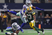 Aaron Jones #33 of the Green Bay Packers evades Jaylon Smith #54 and Robert Quinn #58 of the Dallas Cowboys in the fourth quarter at AT&T Stadium on October 06, 2019 in Arlington, Texas.