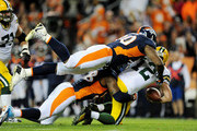 Quarterback Aaron Rodgers #12 of the Green Bay Packers is sacked by Von Miller #58 and Antonio Smith #90 of the Denver Broncos in the fourth quarter at Sports Authority Field at Mile High on November 1, 2015 in Denver, Colorado.