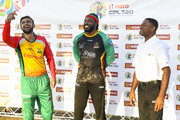 In this handout image provided by CPL T20, Shoaib Malik (L) of Guyana Amazon Warriors toss the coin as Chris Gayle (C) St Kitts & Nevis Patriots and match referee Denavon Hayles (R) look on during the Hero Caribbean Premier League match 2 between Guyana Amazon Warriors and St Kitts & Nevis Patriots at Guyana National Stadium on August 9, 2018 in Providence, Guyana.