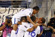 Midfielder Andy Najar #14 of Honduras jumps on his teammates after midfielder Marvin Chavez #17 scored during the second half against Haiti in a 2013 CONCACAF Gold Cup soccer match on July 8, 2013 at Red Bull Arena in Harrison, New Jersey. Honduras defeated haiti 2-0.