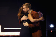 """Ryan Gosling presents Mary Zophres with the Hamilton Award for Costume Designer for """"First Man"""" at the Hamilton Behind the Camera Awards presented by Los Angeles Confidential Magazine on November 4, 2018 in Los Angeles, California.  (Photo by Phillip Faraone/Getty Images for LA Confidential)"""