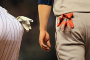 (L-R) Batting gloves hang from the pockets of first baseman Todd Helton #17 of the Colorado Rockies and base runner Trevor Crowe #8 of the Houston Astros during Interleague play at Coors Field on May 30, 2013 in Denver, Colorado.