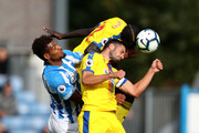 Steve Mounie of Huddersfield Town (L) challenges for the ball with Luka Milivojevic of Crystal Palace and Mamadou Sakho of Crystal Palace during the Premier League match between Huddersfield Town and Crystal Palace at John Smith's Stadium on September 15, 2018 in Huddersfield, United Kingdom.