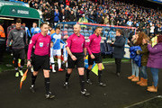 Referee Mike Dean with Assistant referees Eddie Smart and Mark Scholes lead out the teams for the Premier League match between Huddersfield Town and Crystal Palace at John Smith's Stadium on March 17, 2018 in Huddersfield, England.