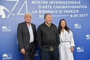 """Chinese artist and producer Ai Weiwei (C), producers Chin-Chin Yap and Heino Deckert (L) attend the photocall of the movie """"Human Flow"""" presented in competition at the 74th Venice Film Festival on September 1, 2017 at Venice Lido.  / AFP PHOTO / Tiziana FABI"""