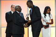 Usain Bolt (2nd R) of Jamaica receives the male athlete of the year award from IAAF President Lamine Diack (2nd L) during the IAAF athlete of the year awards at the IAAF Centenary Gala on November 24, 2012 in Barcelona, Spain.
