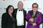 (L-R) Karen Needham, IMDb Founder & CEO Col Needham, and Elton John walk the red carpet at the Elton John AIDS Foundation Academy Awards Viewing Party on February 09, 2020 in Los Angeles, California.